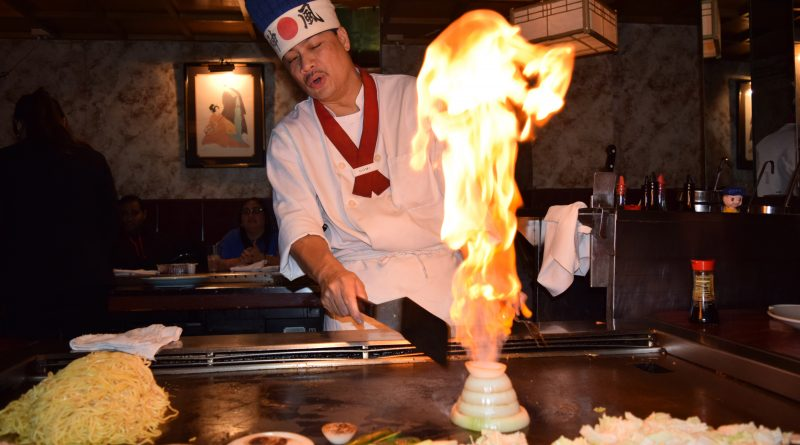 Domi hibachi chef makes a tall fire in the onions.